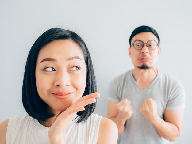 Femme asiatique heureuse et mari perdant en colère.