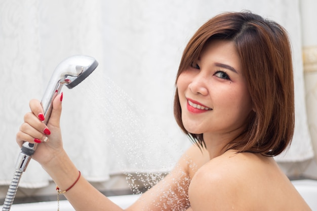 Femme asiatique heureuse prenant une douche dans sa salle de bain