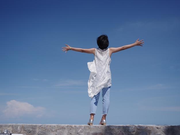 Femme asiatique heureuse et sourire sur la plage et le ciel bleu