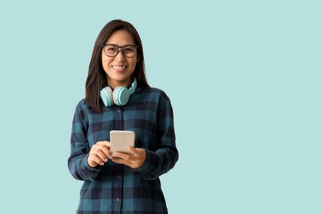 Une femme asiatique heureuse utilise un téléphone portable isolé sur fond bleu