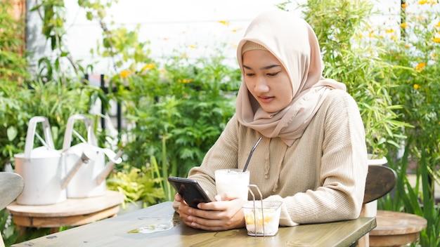 Femme asiatique hijab jouant au téléphone au café