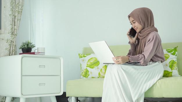 Femme asiatique en hijab en ligne à la maison discutant via mobile