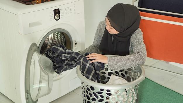 Une femme asiatique en hijab met des vêtements sales dans une machine à laver à la maison