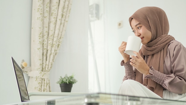 Femme asiatique en hijab travaillant à domicile à l'aide d'un ordinateur portable tout en buvant un verre