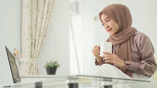Femme asiatique en hijab travaillant à domicile à l'aide d'un ordinateur portable tout en prenant un verre