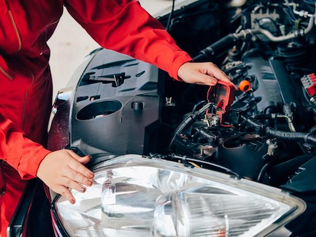 Femme asiatique d'ingénierie réparant une voiture.