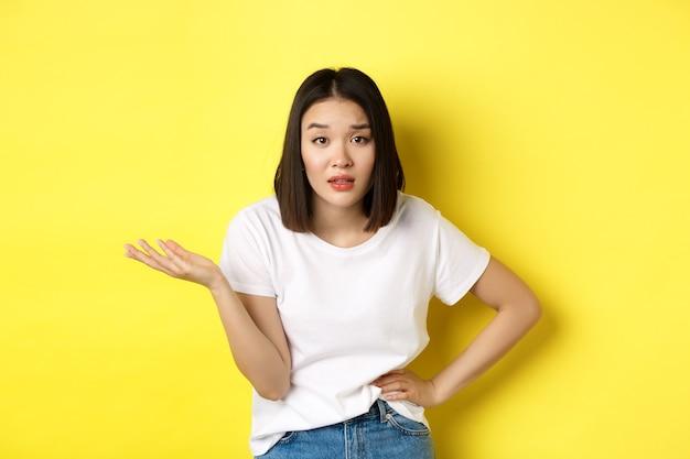 Femme asiatique insouciante demandant ainsi quoi, lever la main et regarder la caméra sceptique, debout sur le jaune.