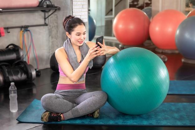 Femme asiatique intelligente sportswear tenant le téléphone à la salle de fitness.