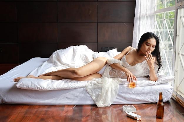 Femme asiatique ivre en lingerie blanche, buvant et fumant en tenant une bouteille d'alcool et allongée sur un lit dans la chambre
