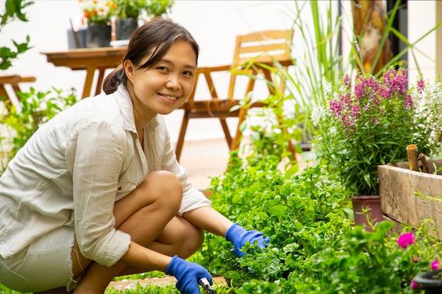 Femme asiatique jardinant votre plante et fleur à l'extérieur.