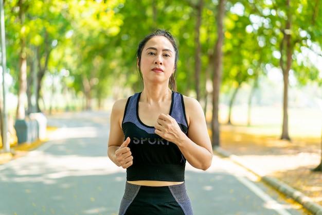 Femme asiatique, jogging, et, courant, à, parc