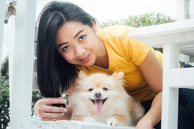 Femme asiatique joue avec son chien poméranien.