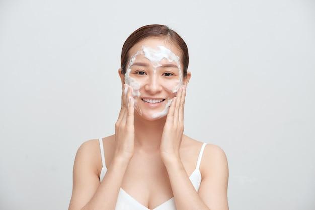 Une femme asiatique joyeuse appliquant un nettoyant moussant a une peau propre et saine.