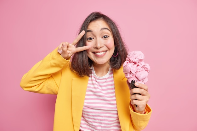 Une femme asiatique joyeuse et joyeuse fait un signe de victoire sur des sourires oculaires tient à pleines dents une grosse glace en cône dans une gaufre vêtue de vêtements élégants s'amuse pendant une chaude journée d'été isolée sur un mur rose.