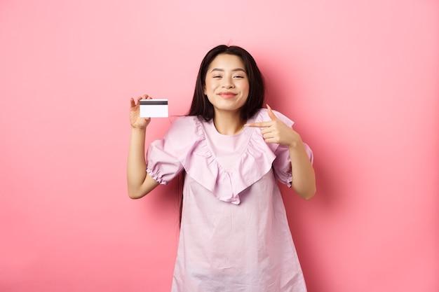 Femme asiatique joyeuse et mignonne souriante satisfaite, montrant une carte de crédit en plastique, debout en robe sur fond rose.