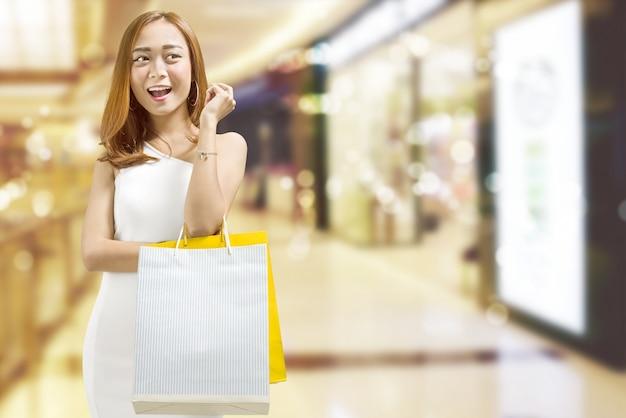 Femme asiatique joyeuse, portant des sacs dans le centre commercial