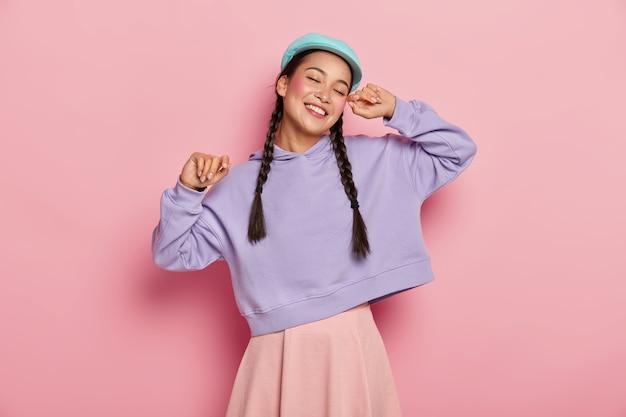 Une femme asiatique joyeuse et sans soucis garde les mains levées, danse contre le mur rose, a les yeux fermés, se fait plaisir avec sa musique préférée