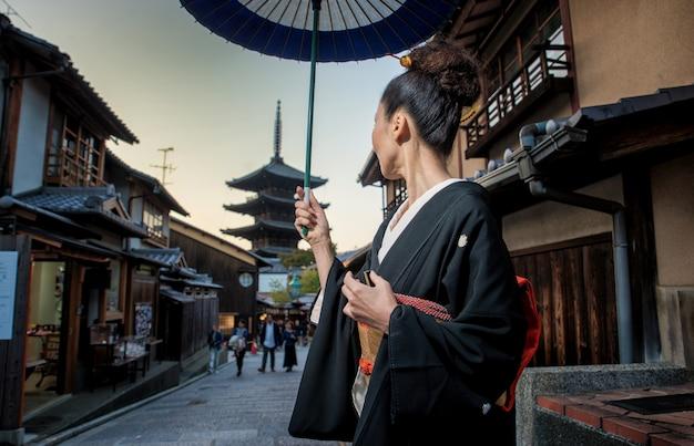 Femme asiatique avec kimono marchant à la pagode yasaka à kyoto