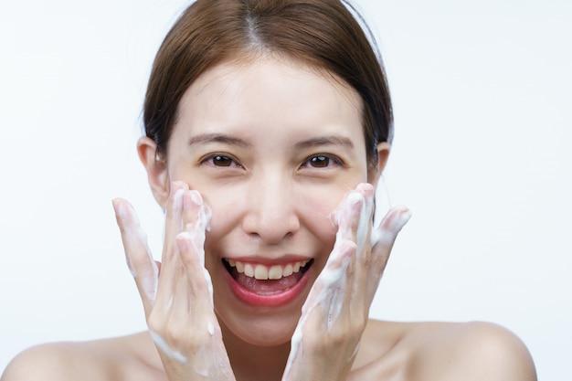 Femme asiatique laver son visage avec de la mousse nettoyante à bulles isolée sur blanc.
