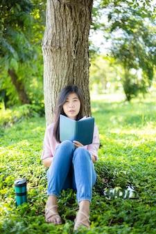 Femme asiatique lisant un livre et souriant dans le parcfemme asiatique satisfaite lisant un livre dans un parc