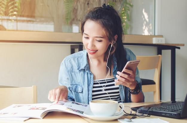 Femme asiatique lisant un magazine dans un café. concept d'entreprise.
