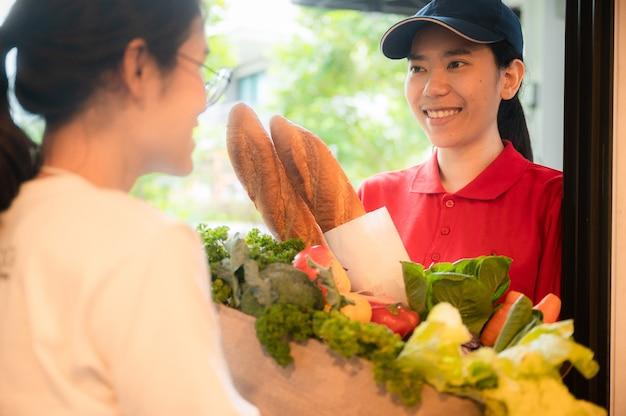 Femme asiatique livrer un sac de nourriture, donner au client devant la maison