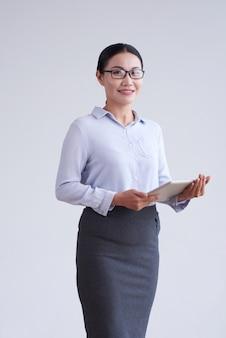 Femme asiatique à lunettes, chemisier élégant et jupe qui pose en studio avec tablette