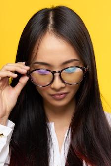 Femme asiatique avec des lunettes étudiant close-up fond jaune. photo de haute qualité
