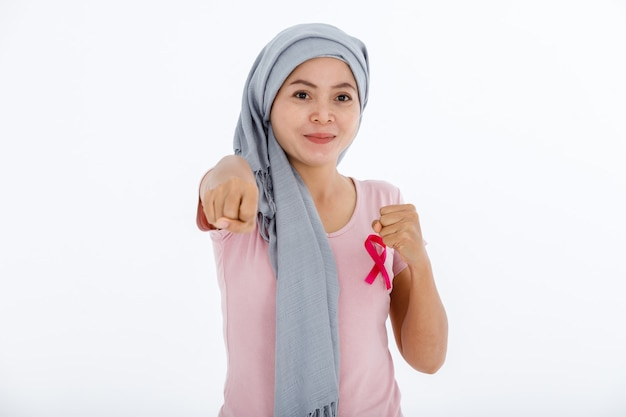 Une femme asiatique malade du cancer mammaire combattant des gants de boxe mois de sensibilisation au cancer du sein isolé sur fond de studio espace copie vierge blanche, soins de santé, concept de médecine