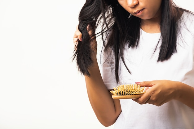 Femme asiatique malheureuse cheveux faibles sa tenir la brosse à cheveux avec des cheveux longs endommagés dans la brosse peigne