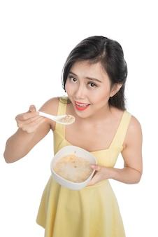 Femme asiatique mangeant un bol de céréales ou de muesli pour le petit déjeuner