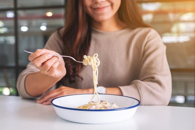 Une femme asiatique mangeant des spaghettis à la carbonara