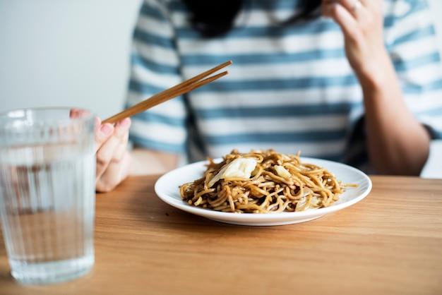 Femme asiatique, manger, nouilles