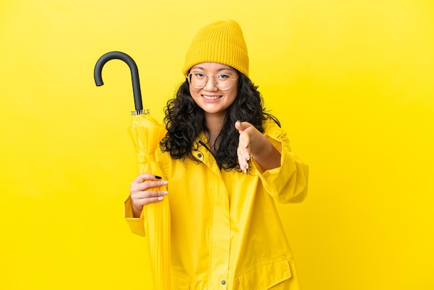 Femme asiatique avec manteau imperméable et parapluie isolé sur fond jaune se serrant la main pour conclure une bonne affaire
