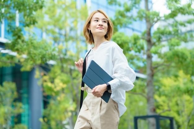 Femme asiatique marchant dans un quartier de bureaux verts