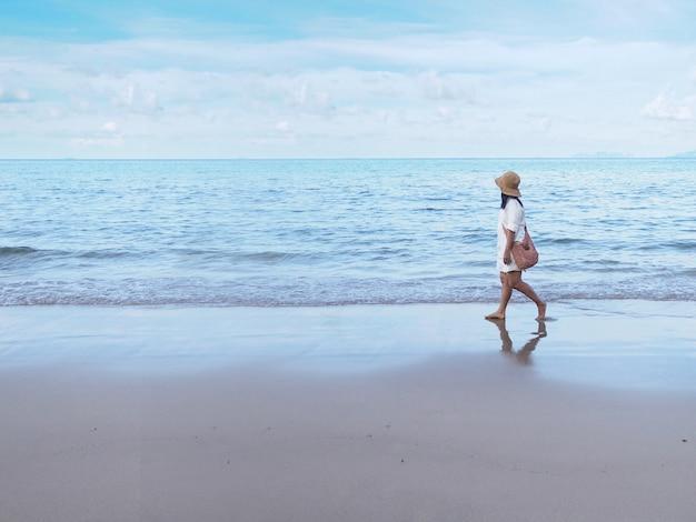Femme asiatique marchant seule sur le sable le long de la plage le matin.