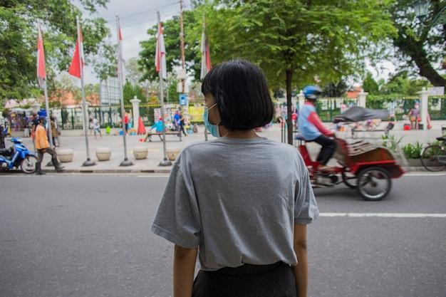 Femme asiatique avec masque médical traversant la route