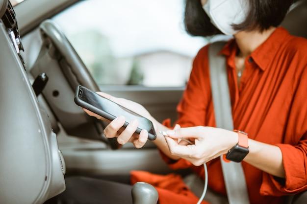 Femme asiatique en masque de protection au volant d'une voiture sur route. charger son téléphone