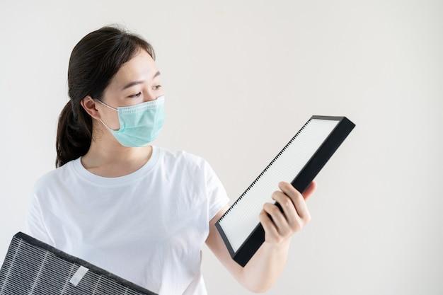Femme asiatique avec masque de protection hygiène pour changer un filtre purificateur d'air hepa