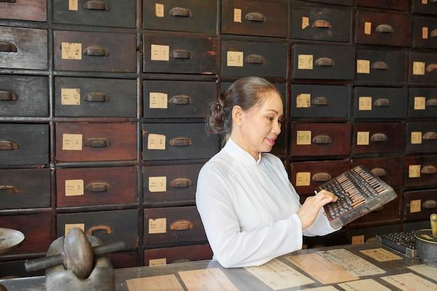 Femme asiatique mature comptant sur boulier