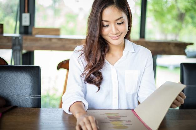 Femme asiatique menu ouvert pour commander dans un café-restaurant et un sourire pour un moment heureux