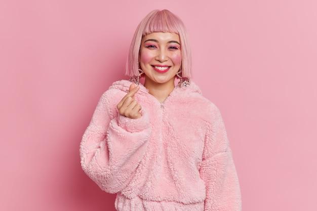 Une femme asiatique à la mode avec un maquillage brillant fait un mini geste de coeur coréen comme un signe qui sourit agréablement a les cheveux roses et un manteau de fourrure pose des robes d'intérieur pour une soirée disco. concept de langage corporel.