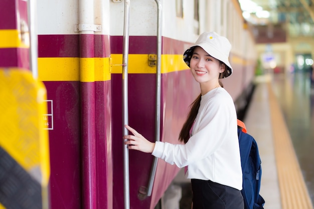 Une femme asiatique montait dans le train pour voyager pendant que le train était garé sur le quai