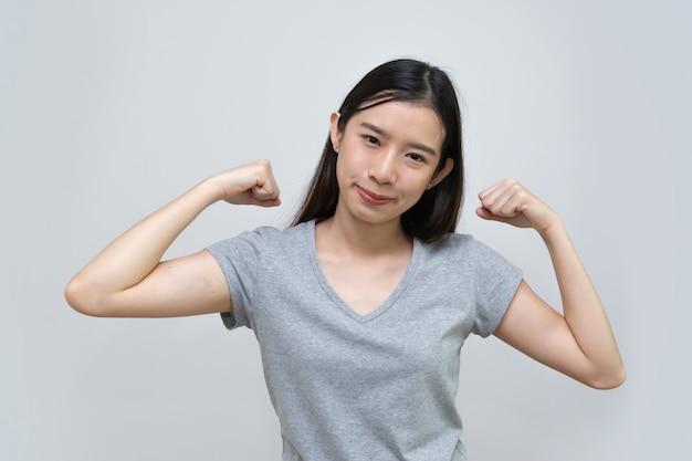 Femme asiatique montre un bras puissant, belle jeune femme
