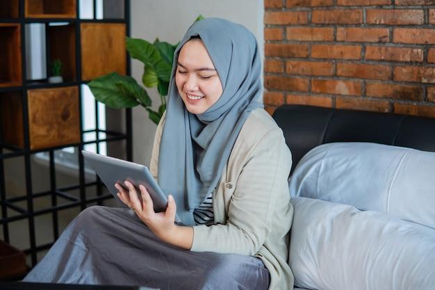 Femme asiatique musulmane à l'aide de tablette assise sur le lit