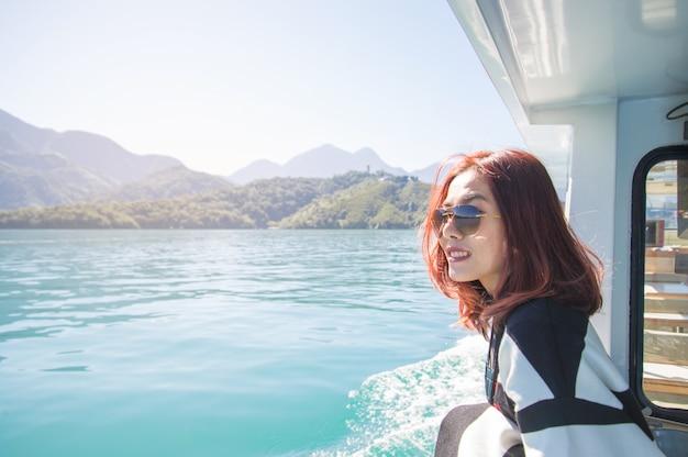 Une femme asiatique navigue sur un yacht en mer, regardant au loin. journée ensoleillée