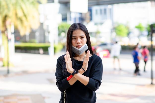 Femme asiatique ne porte pas de masque facial pour la protection contre le virus ou la pollution. signe de la main incorrect sur fond de prople extérieure. nouveau concept normal. signe.