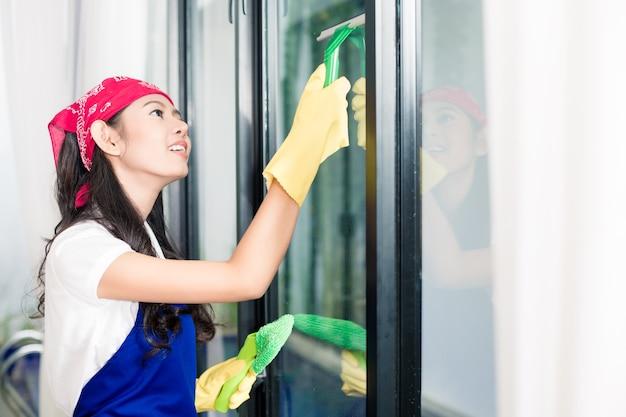 Femme asiatique nettoyant les fenêtres de sa maison en profitant de la corvée