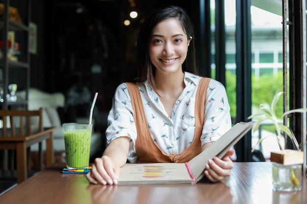 Femme asiatique ouvre le menu pour commander au café