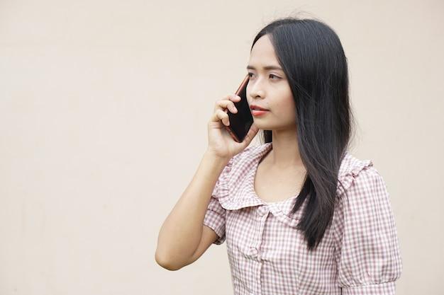 Femme asiatique parlant au téléphone au sujet des affaires